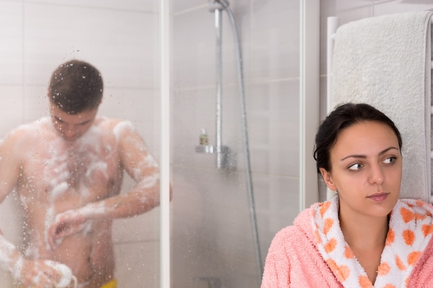 남자친구가 욕실에 투명한 유리문이 있는 샤워실에서 거품 스펀지 목욕을 하는 동안 기다리는 젊은 여성