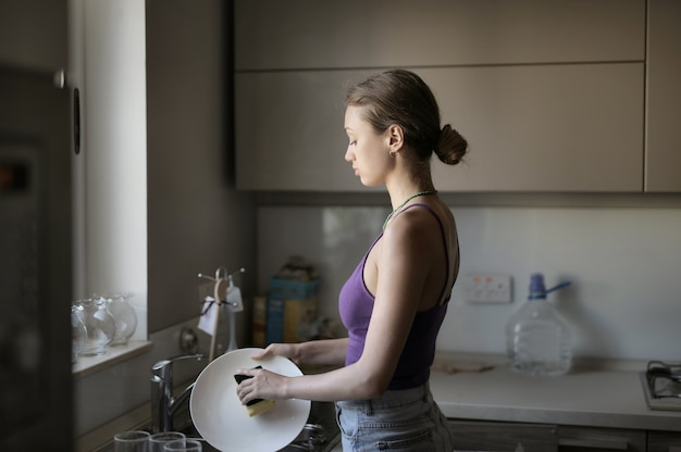 Young female washing the dishes in the kitchen under the lights