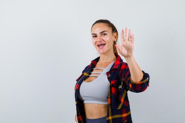 クロップトップ、市松模様のシャツ、パンツで挨拶するために手を振って幸せそうに見える若い女性。正面図。