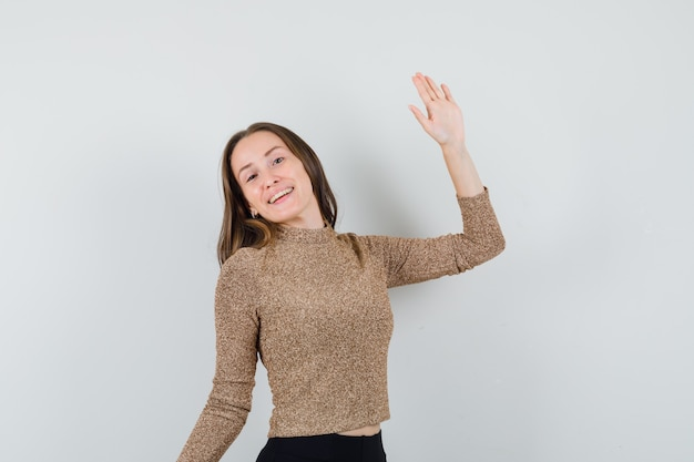 Young female waving hand for goodbye in blouse,skirt and looking cute , front view.