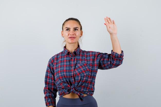 Giovane femmina agitando la mano per il saluto in camicia a scacchi, pantaloni e guardando fiducioso, vista frontale.