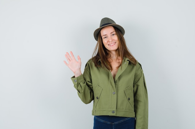 Young female waving hand to say goodbye in jacket, pants, hat and looking cheery. front view.