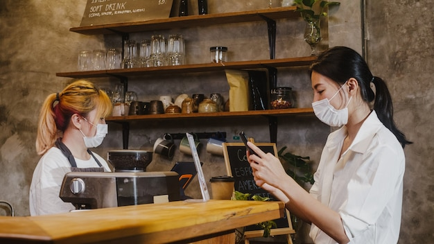 Young female wear face mask self service use mobile phone pay contactless at restaurant.