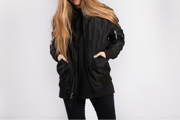 흰 벽에 서 있는 검은 재킷을 입은 젊은 여성