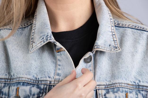 흰 벽에 서있는 블루 진 재킷을 입고 젊은 여성