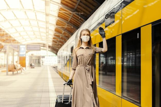 フェイスマスクと手袋を着用し、駅で手を振っている若い女性-covid-19