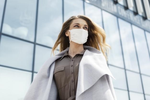 현대적인 건물이 있는 안면 마스크를 쓴 젊은 여성