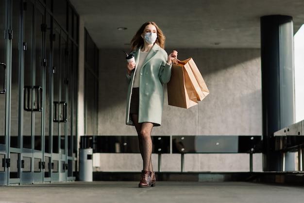ヨーロッパの狭い通りで買い物袋でウイルスを防ぐためにマスクを身に着けている若い女性。