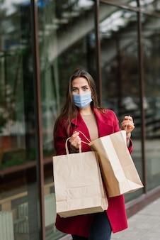 유럽의 좁은 거리에서 쇼핑백으로 바이러스를 예방하기 위해 마스크를 쓰고있는 젊은 여성.