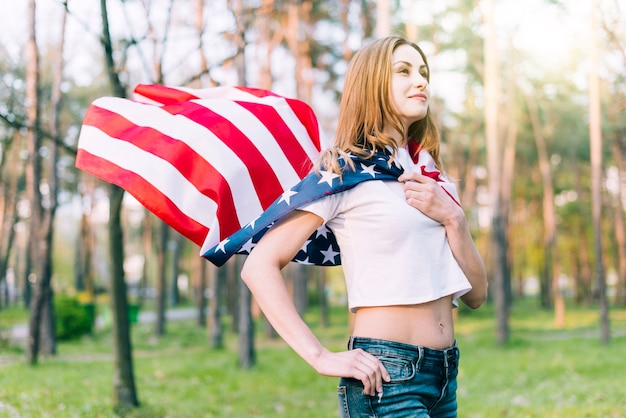 Young female wearing american flag as cape