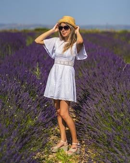 Giovane donna che indossa un bel vestito che cammina in un campo di lavanda in una giornata di sole