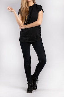 Young female wearing black short sleeve t-shirt standing against a white wall