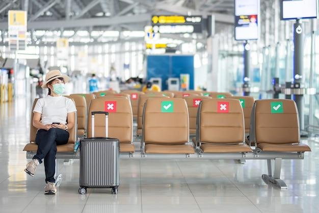 フェイスマスクを着用し、空港で椅子に座っている若い女性、保護コロナウイルス感染症(covid-19)感染、アジアの女性旅行者。ニューノーマル、旅行バブル、社会的距離