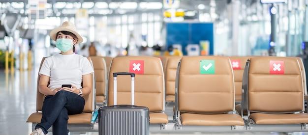 얼굴 마스크를 착용하고 공항에서 의자에 앉아 젊은 여성