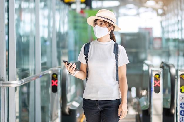 フェイスマスクを着用し、空港で携帯電話を使用して若い女性