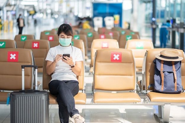 얼굴 마스크를 착용하고 공항에서 모바일 스마트 폰을 사용하는 젊은 여성