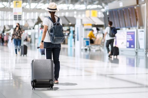 Молодая женщина в маске с багажом проверяет время полета в аэропорту