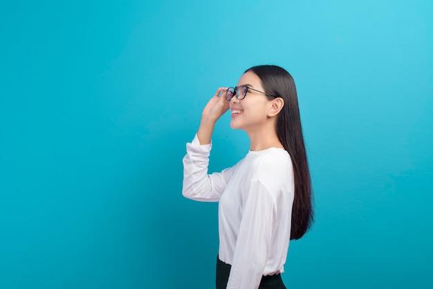 青い背景の上の眼鏡をかけている若い女性