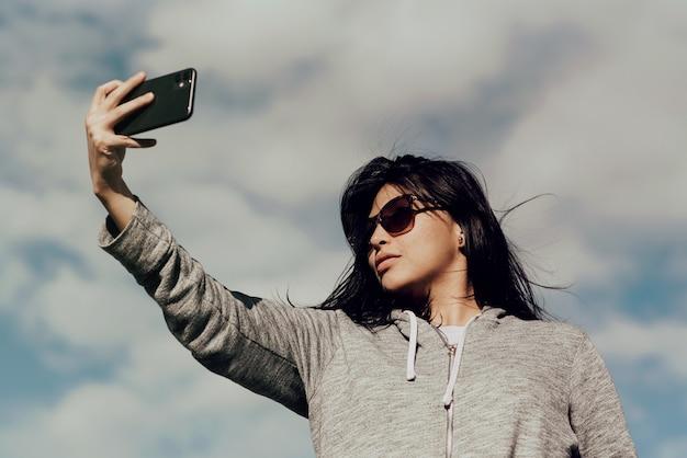 曇った青い空の下で彼女の携帯電話で写真を撮るサングラスをかけている若い女性