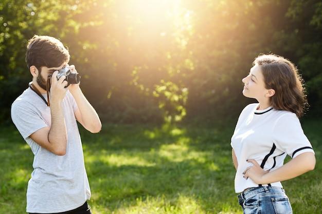 Футболка молодой женщины нося представляя в камере к фотографу. молодой талантливый кобель с ретро камерой фотографирует хорошенькую самку