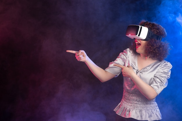 Young female wearing virtual reality headset on dark blue surface