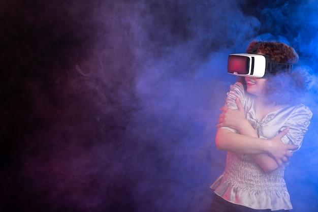 Giovane donna che indossa le cuffie da realtà virtuale sulla superficie blu scuro