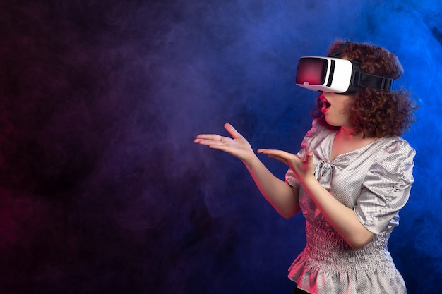 Young female wearing virtual reality headset on dark smoky play game videos