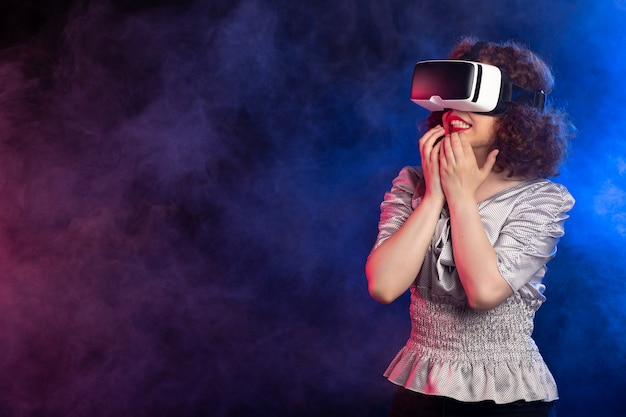 Young female wearing virtual reality headset on dark smoky play video game
