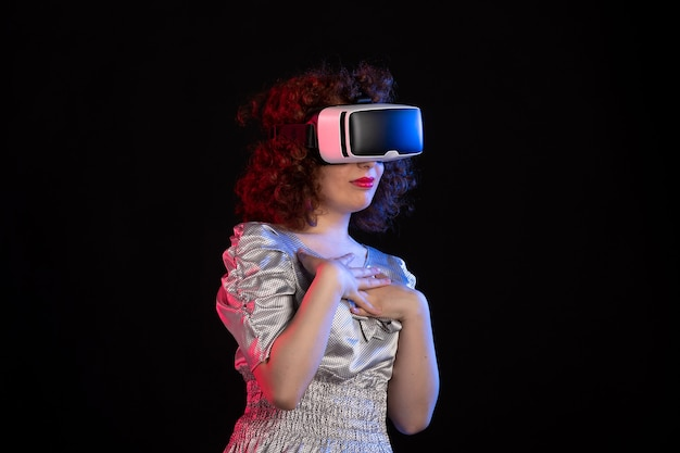 Young female wearing virtual reality headset on dark surface