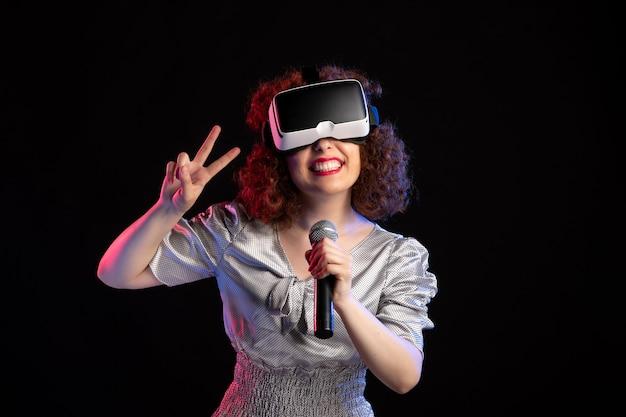 Giovane donna che indossa le cuffie da realtà virtuale con microfono