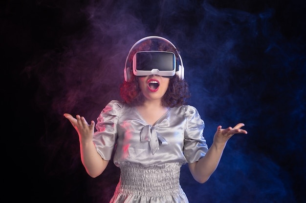 Young female wearing vr headset in headphones on dark surface