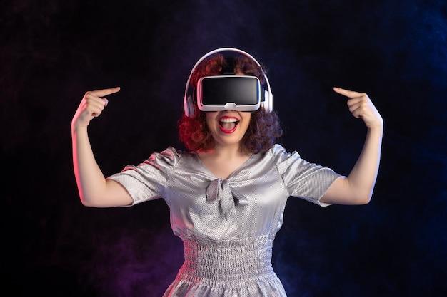 Молодая женщина носить гарнитуру vr в наушниках на темной поверхности