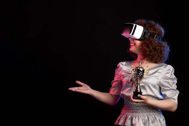 Giovane femmina che indossa la cuffia avricolare del vr con la tazza sulla scrivania scura d videogioco per videogiochi