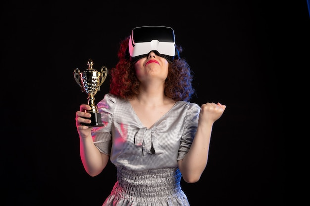 Young female wearing vr headset with cup on dark floor video gaming vision game play
