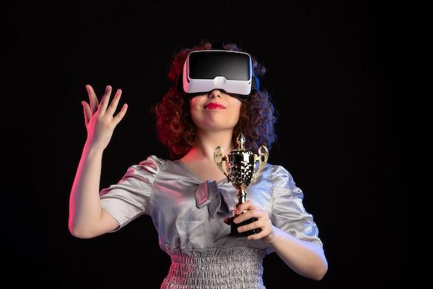 Giovane donna che indossa l'auricolare vr con tazza sul gioco di visione di videogiochi scuri