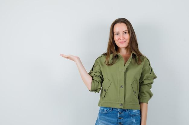 젊은 여성을 환영하거나 재킷, 반바지에 뭔가를 보여주는 자신감, 전면보기를 찾고.