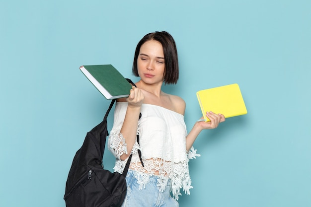 Young female in white shirt blue jeans and black bag holding copybooks on blue
