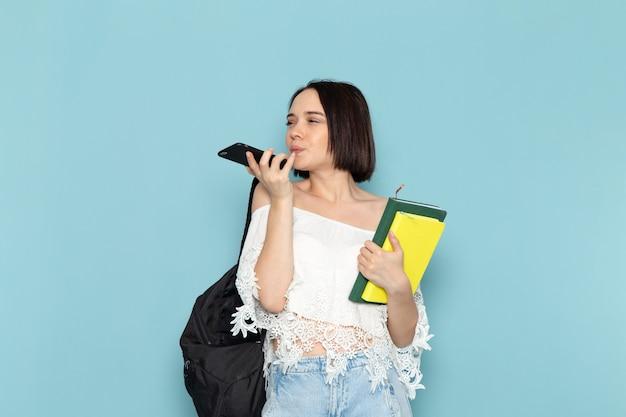 Giovane donna in camicia bianca blue jeans e borsa nera in possesso di quaderni e telefono blu