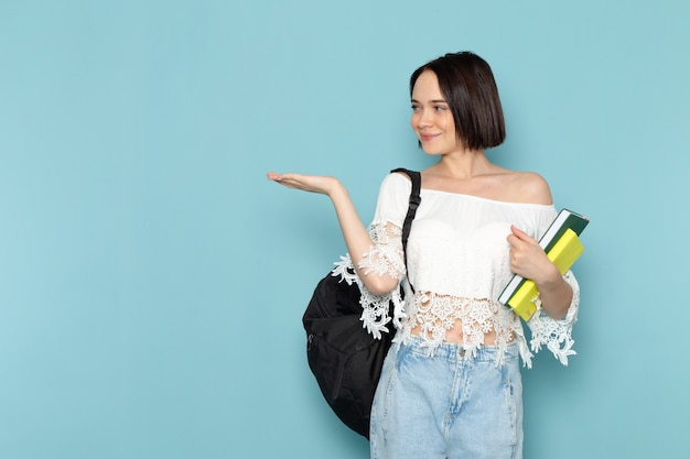 Young female in white shirt blue jeans and black bag holding copybooks smiling on blue