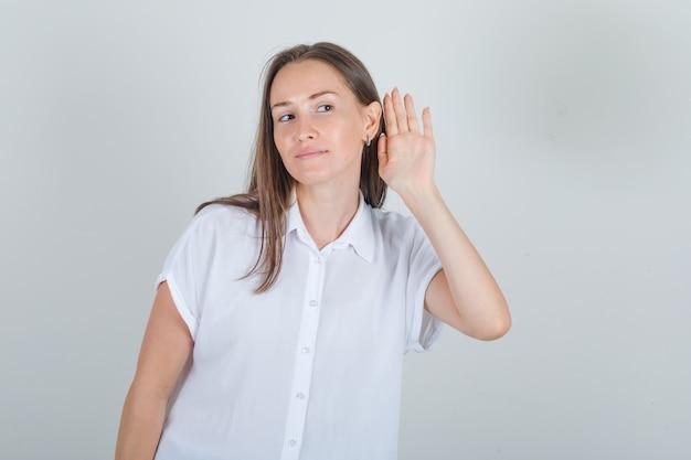 Giovane femmina in camicia bianca che tiene la mano all'orecchio