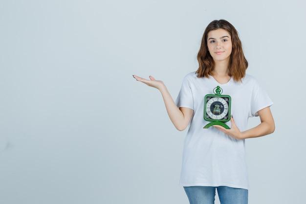 Giovane donna in maglietta bianca, jeans che tengono l'orologio, mostrando il gesto di benvenuto e guardando allegro, vista frontale.