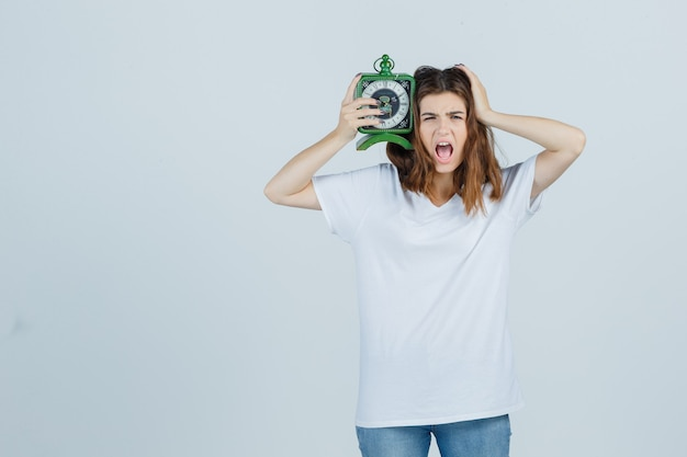 Giovane donna in maglietta bianca, jeans che tengono l'orologio mentre urla e sembra ansiosa, vista frontale.