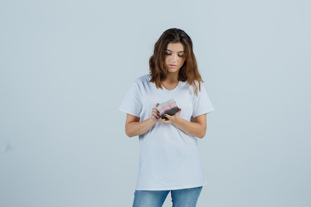 Young female in white t-shirt, jeans looking at gift box and looking hesitant , front view.