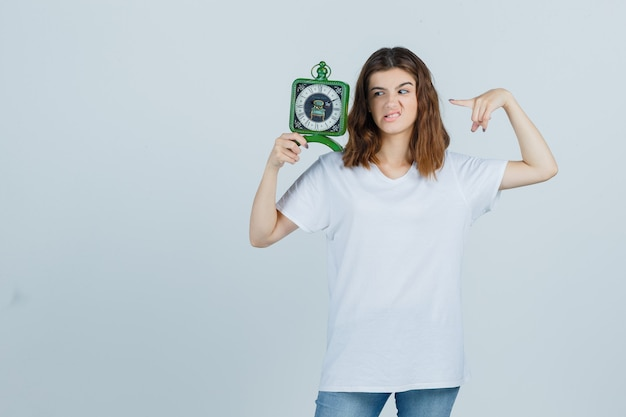 Young female in white t-shirt, jeans pointing at clock, frowning face and looking troubled , front view.
