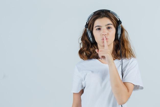 Giovane donna in maglietta bianca che mostra gesto di silenzio e guardando attento, vista frontale.