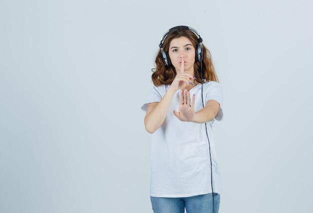 Giovane donna in maglietta bianca che mostra il gesto di silenzio con il segno di silenzio e guardando attento, vista frontale.