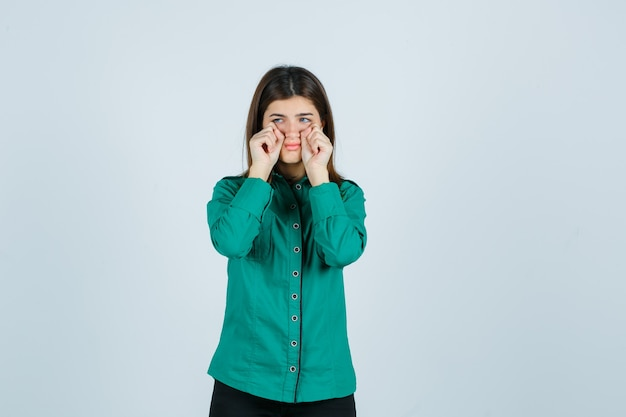 緑のシャツを着た手で涙を拭き、気分を害した若い女性。正面図。