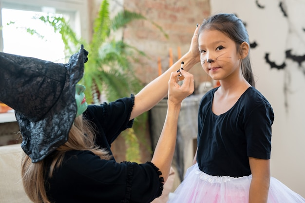 Young female in witch hat and black pullover applying halloween makeup on face of cute girl