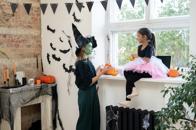 Young female in witch hat and little girl with pumpkins