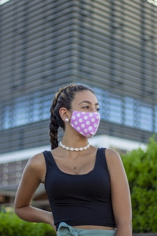晴れた日にカメラでポーズをとる医療マスクを持つ若い女性-ニューノーマルの概念